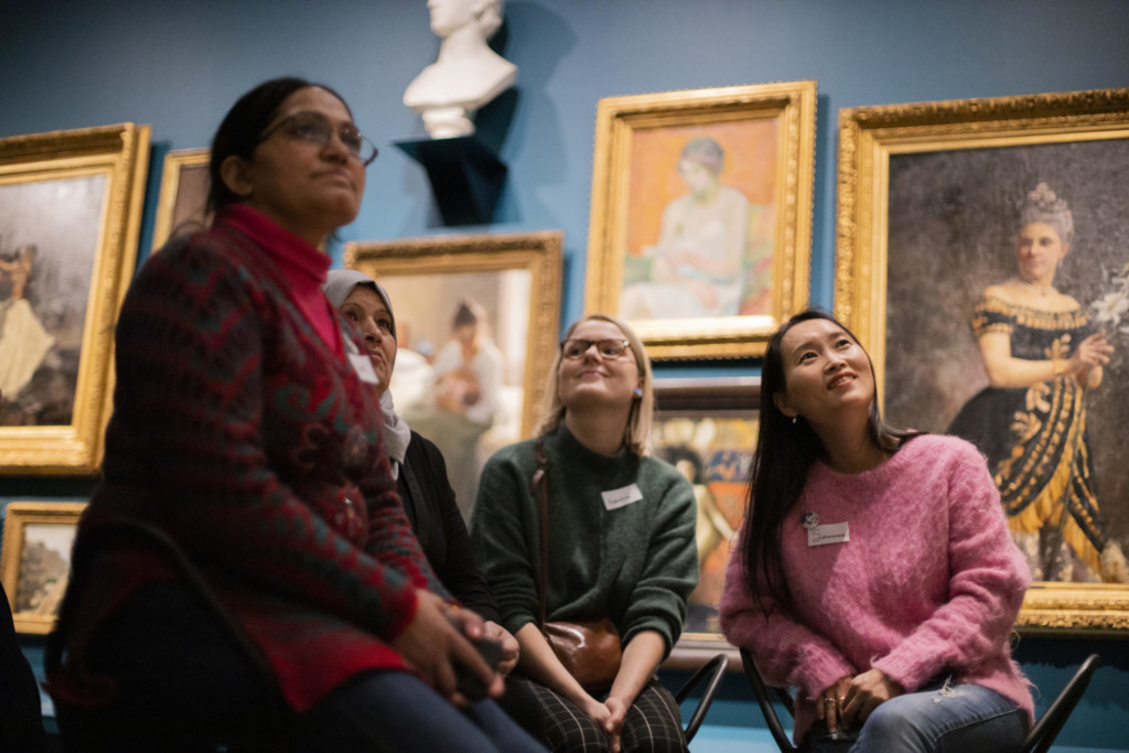 Museum visitors are sitting at a gallery space.