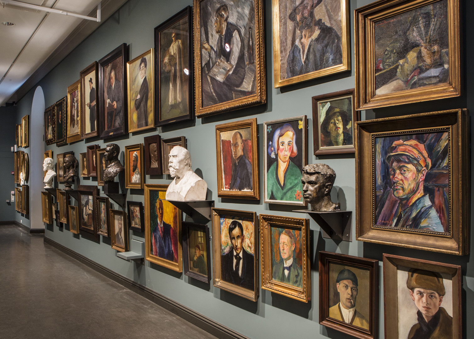 Taiteilijoiden omakuvakuvia ripustettuna tiheästi seinälle.