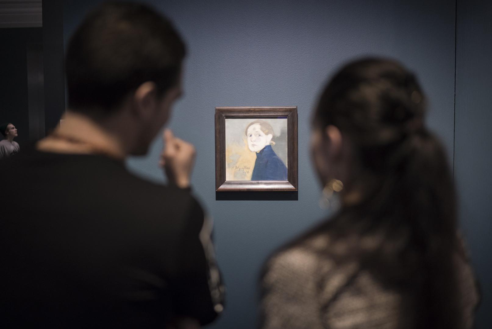 Kaksi henkilöä katsoo Helene Schjerfbeckin muotokuvaa.