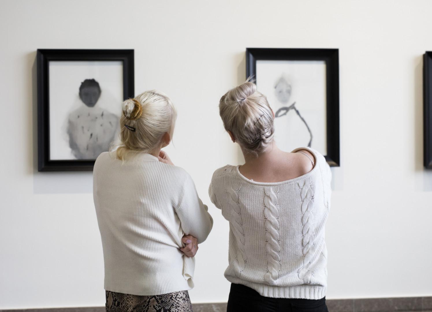 Kaksi henkilöä katsoo taideteoksia mietteliäinä