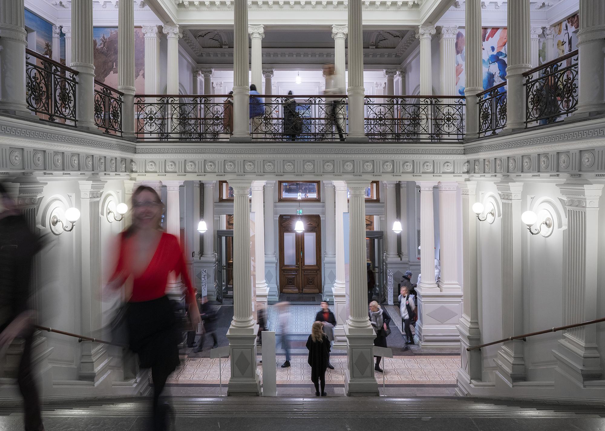 Ihmisiä Ateneumin aulassa ja portaikossa ilmaispäivänä.