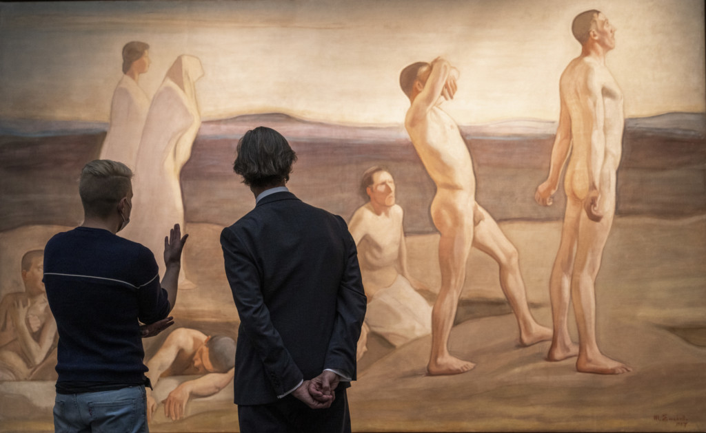 Two museum visitors looking at a painting in the Magnus Enckell exhibition.
