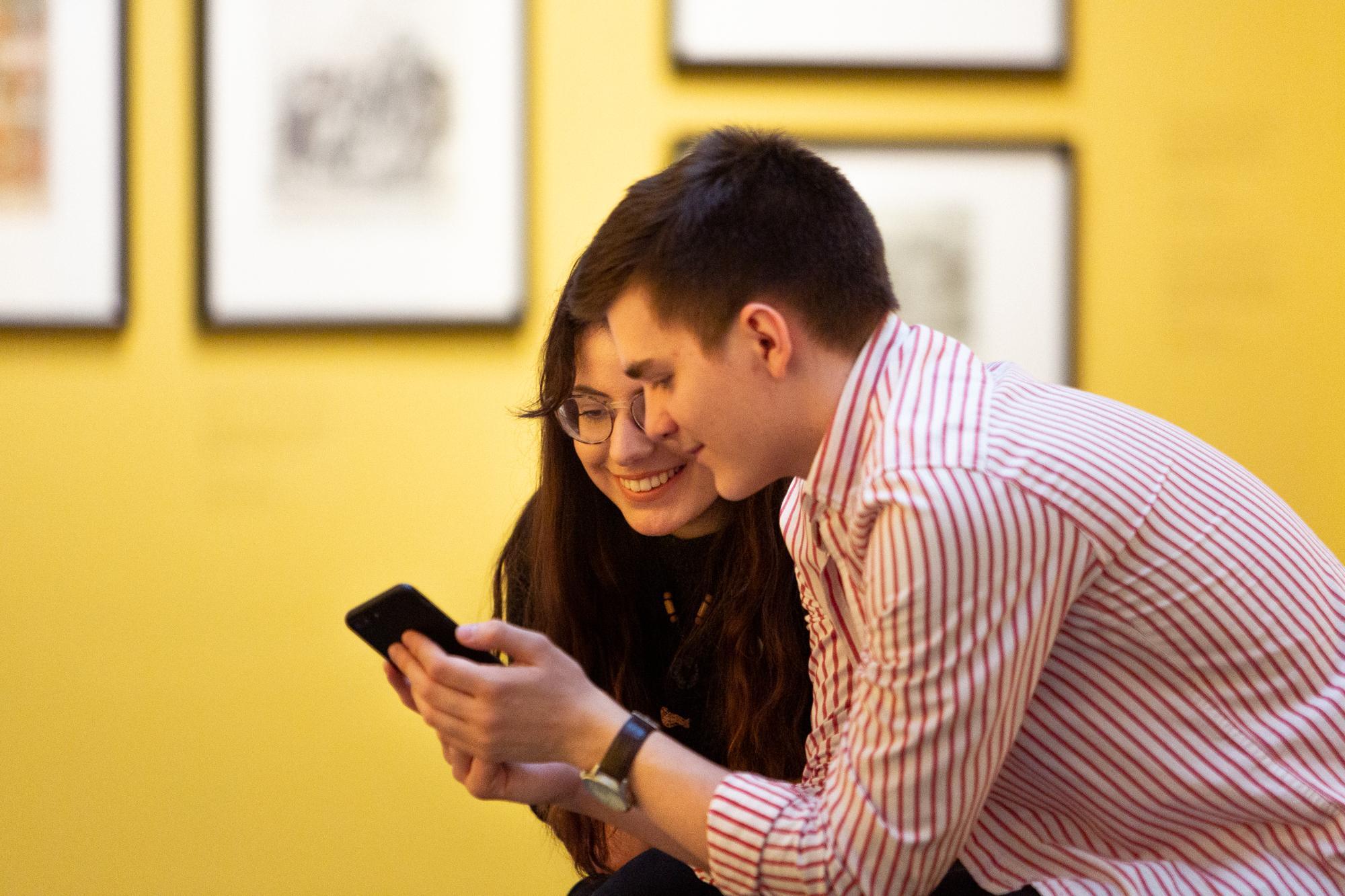 Kaksi asiakasta tarkastelevat puhelinta iloisina näyttelytiloissa.