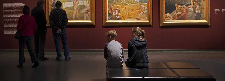 Suomen taiteen tarina -näyttelytiloissa; edustalla penkki, jossa istuu kaksi lasta vierekkäin. Taaempana kolme maalausta vierekkäin ja niitä katselemassa kolme aikuista.