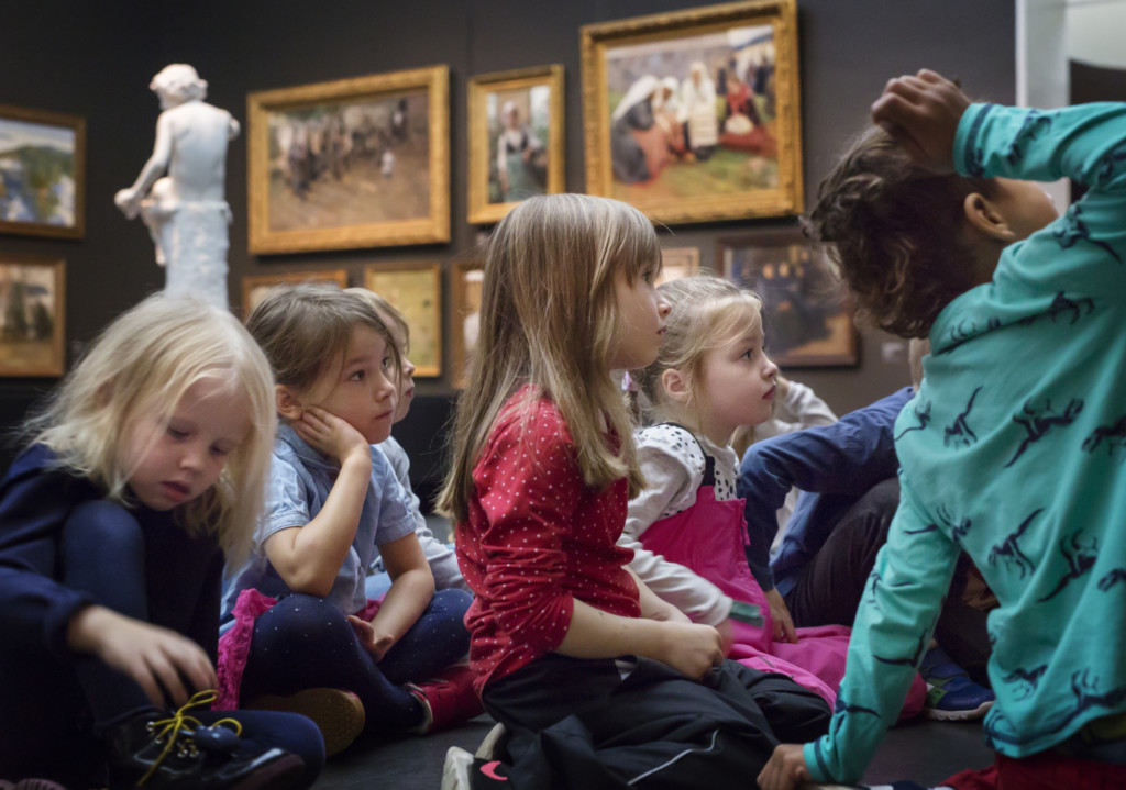 Lapsia kuuntelemassa Suomen taiteen tarina -näyttelyn opastusta näyttelytiloissa.