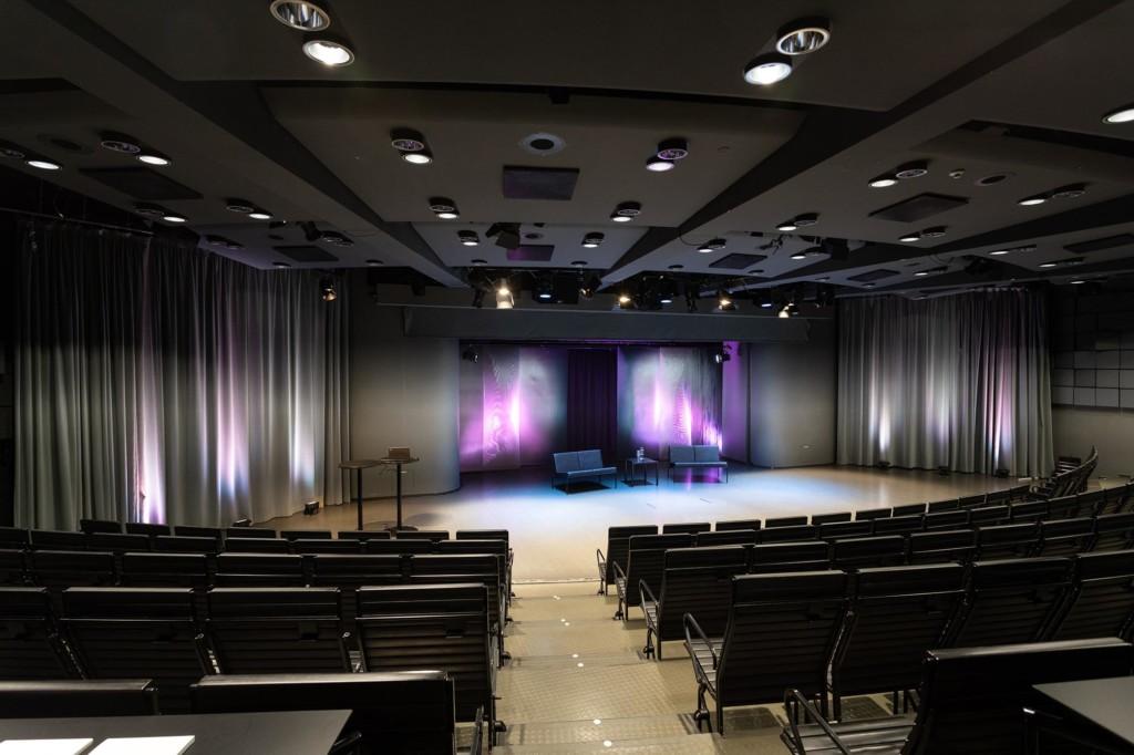 Laskeva auditorio, jossa pitkiä penkkirivejä neljä. Lavalla kaksi sohvaa ja lavan takan koristeellisesti valaistut verhot.