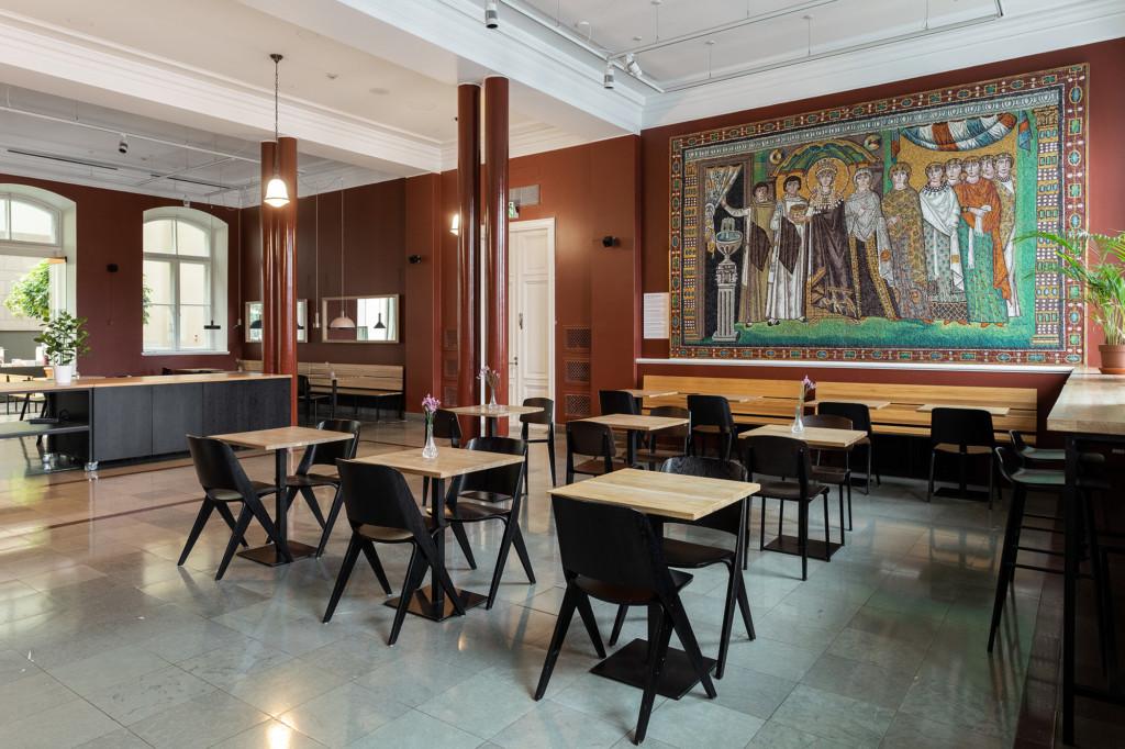 Kahvilanäkymä, jossa muutama yksittäisiä pöytiä tuolineen. Takana koko seinän peittävä mosaiikkiteos.