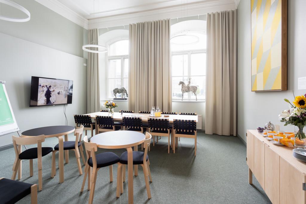 Kokoushuone, jossa edustalla kaksi pienempää pyöreää pöytää ja kauempana suurempi pitkä pöytä. Kuvan oikealla alakulmassa lipasto, jonka päälle on asetettu kahvitarjoilut ja kukka-asetelma.