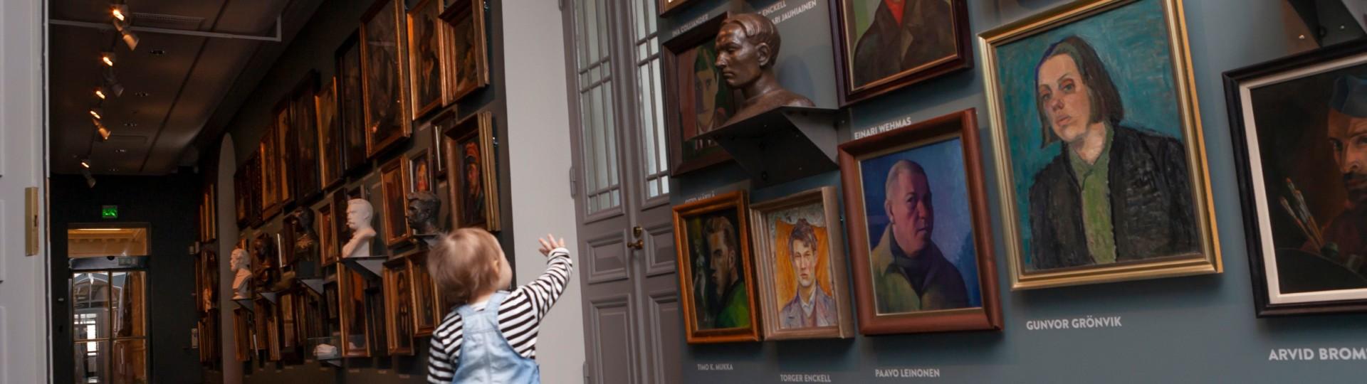 Lapsi vilkuttaa muotokuvateoksille Suomen taiteen tarina -näyttelyssä.
