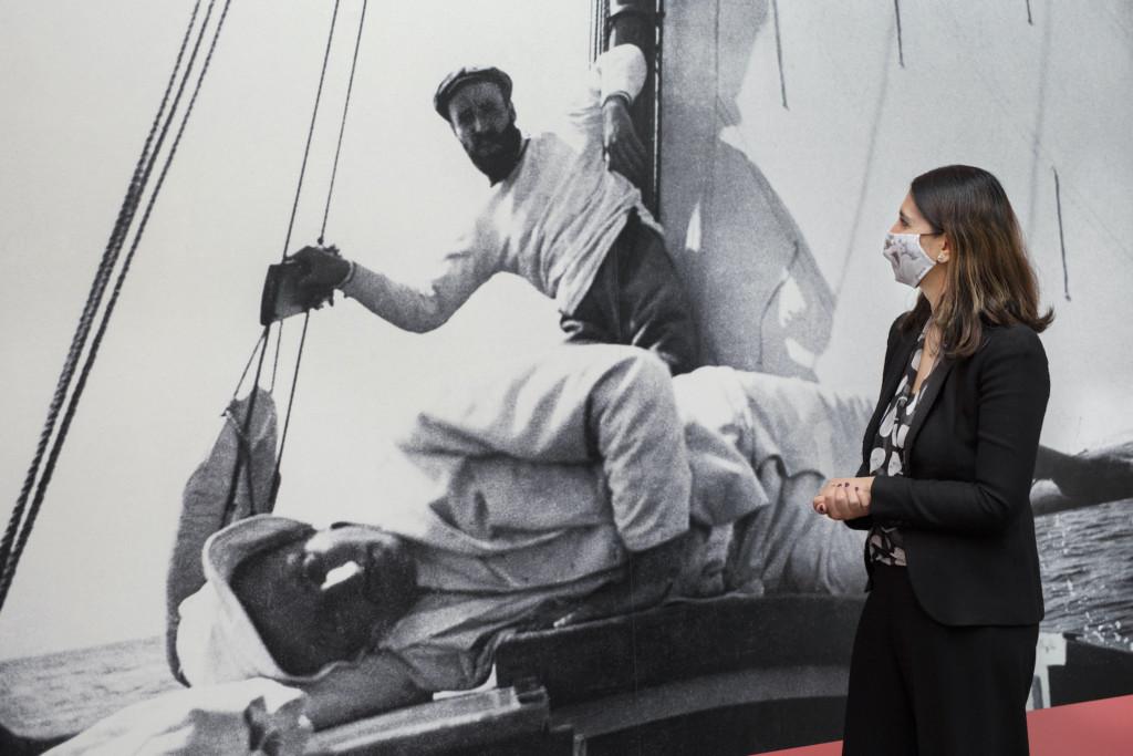 Helsingin apulaispormestari Nasima Razmyar katsoo valokuvaa Magnus Enckellistä ja Hugo Simbergistä purjehtimassa.