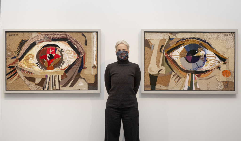 Anne Liljeström seisoo kahden Karin Hellmanin silmä-aiheisen taideteoksen välissä.
