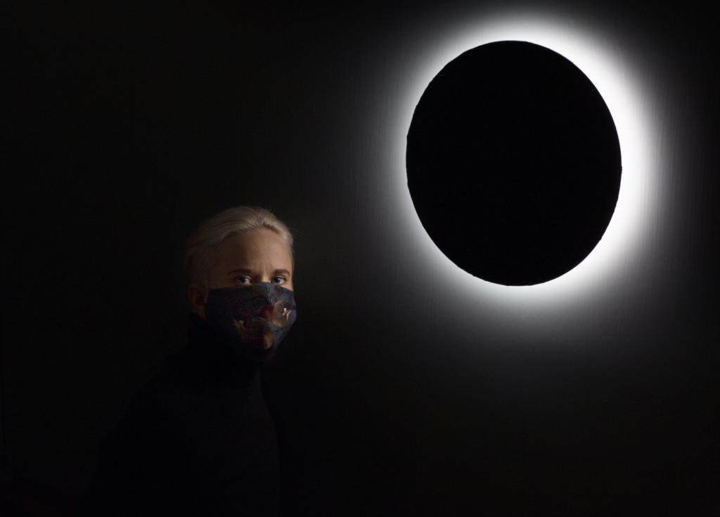 Anne Liljeström seisoo pimeydessä pyöreän valaisimen vieressä.
