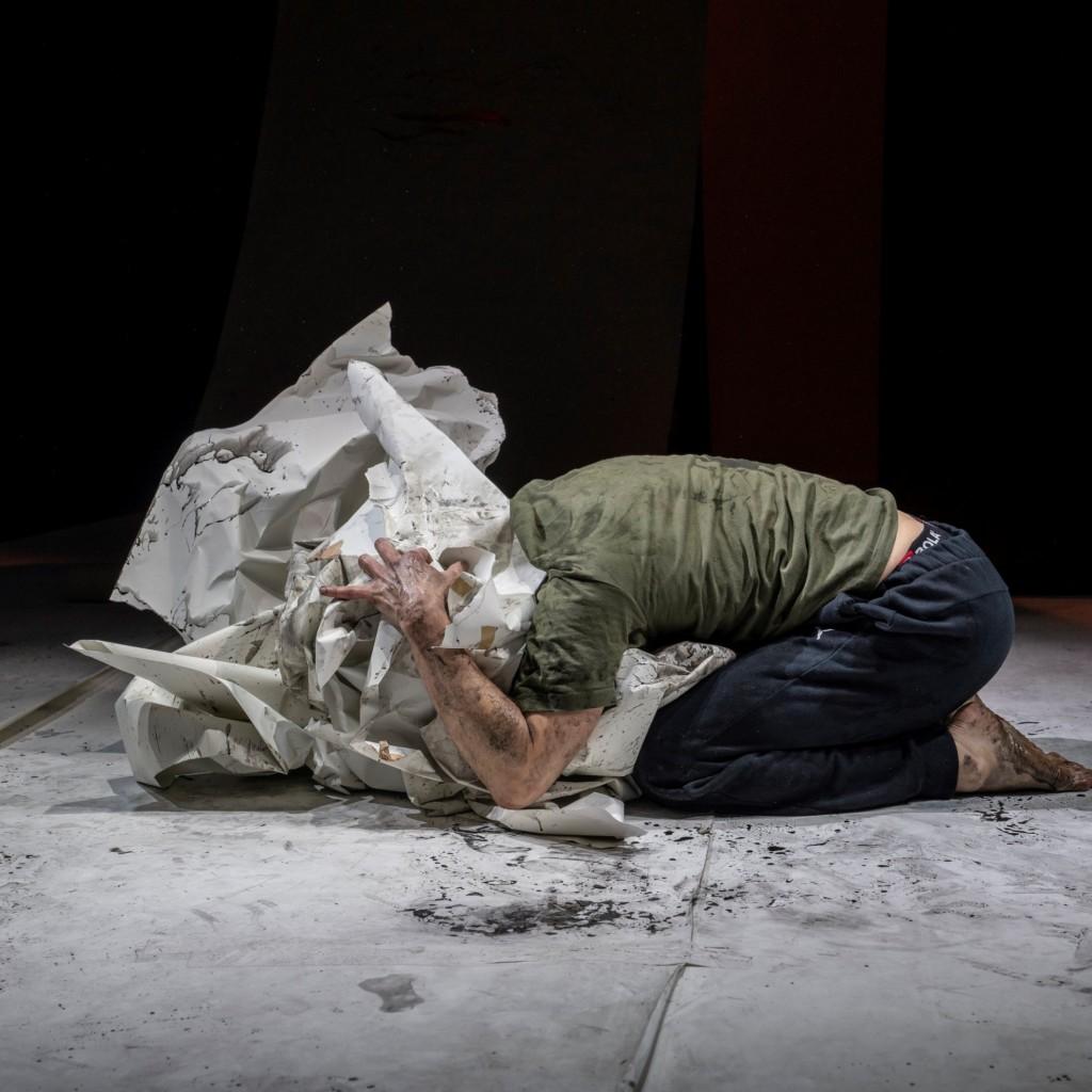 Kuva esityksestä: mies on kumartunut lattialla polviensa päälle, päänsä hän on piilottanut paperiin