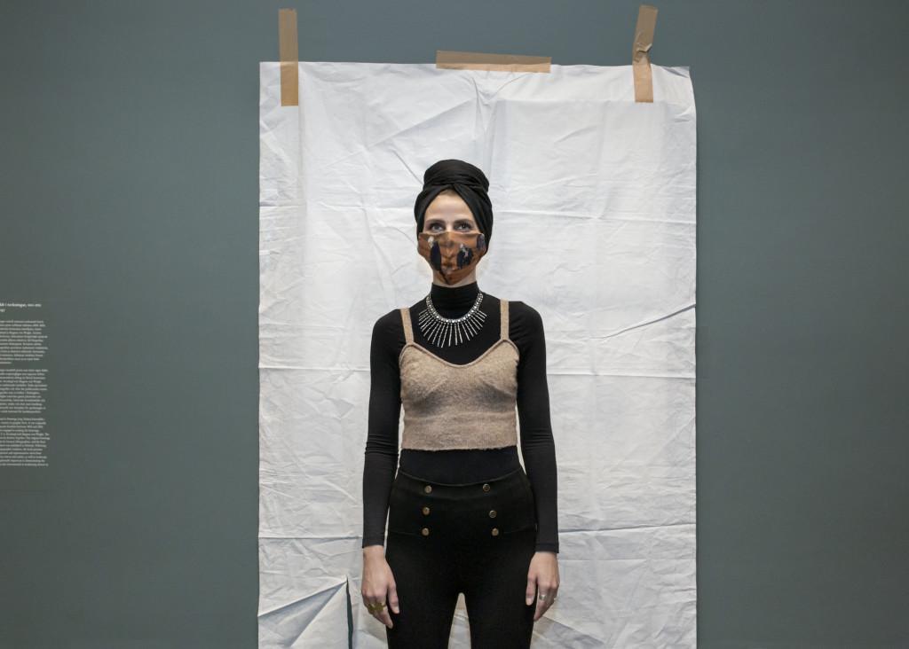 Nainen, jolla on turbaani päässä ja maski kasvoilla, seisoo valkoisella paperilla peitetyn teoksen edessä Ateneumissa.