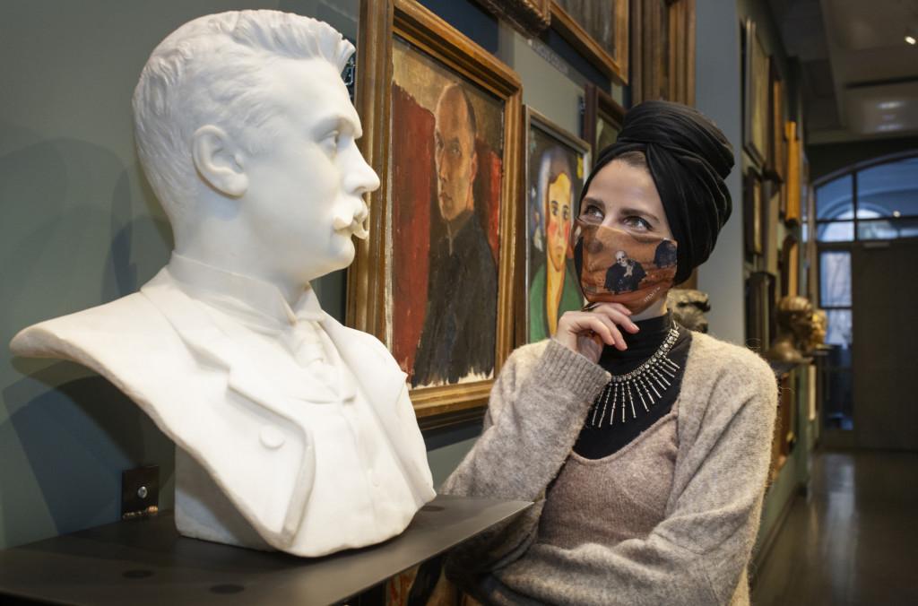 Nainen, jolla on turbaani päässä ja maski kasvoilla, katsoo Albert Edelfeltin rintakuvaa Ateneumissa.