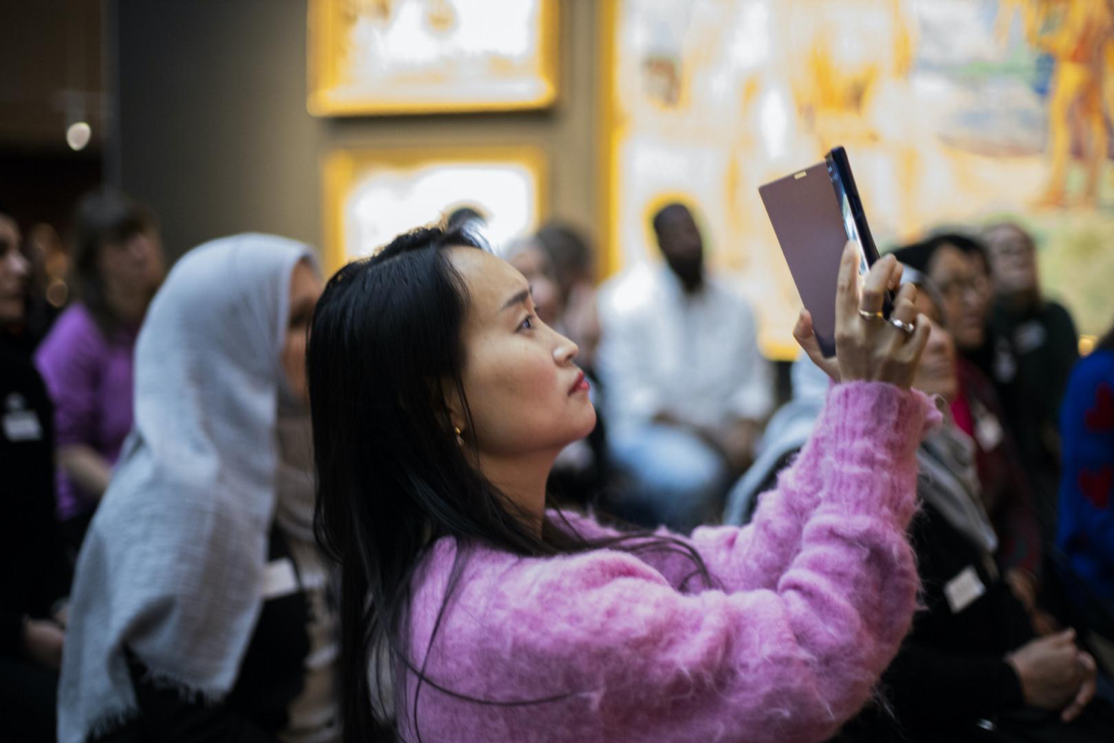 Museovieras ottaa valokuvaa puhelimellaan.