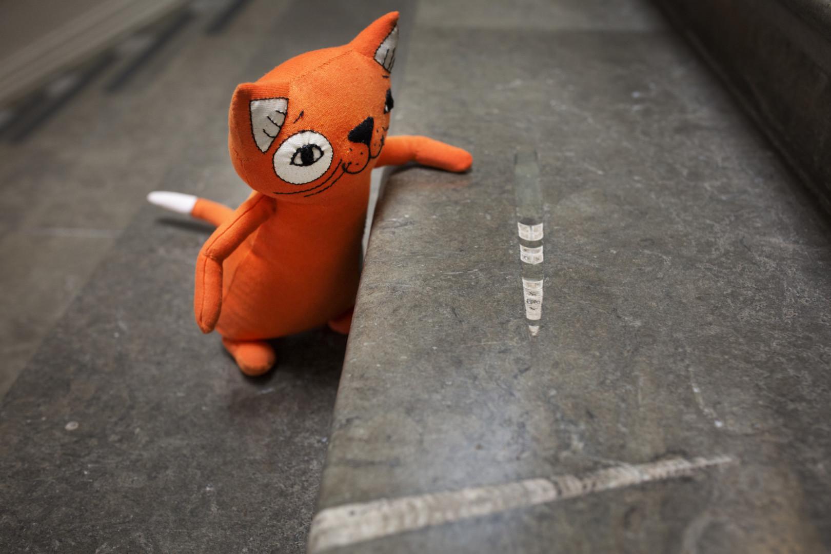 Ateneumin maskottina toimiva oranssi pehmolelukissa kiipeää Ateneumin portaita.