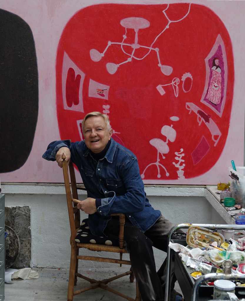 Man sits on a chair, a red-coloured painting on the background, painting equipment on the foreground.