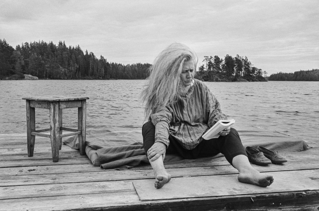 A woman sits on a dock by a lake, reading a book barefeet. Black and white photo.