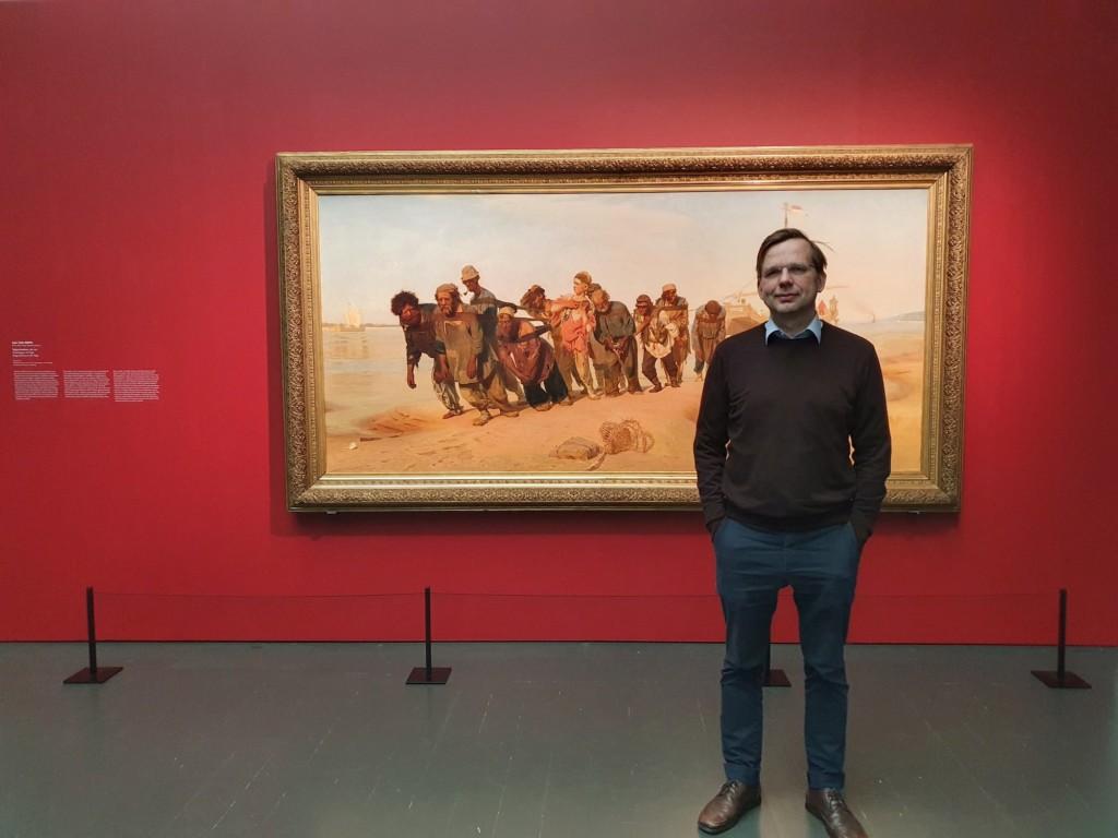 Mies seisoo Ilja Repinin Volgan lautturit -maalauksen edessä taidenäyttelyssä.