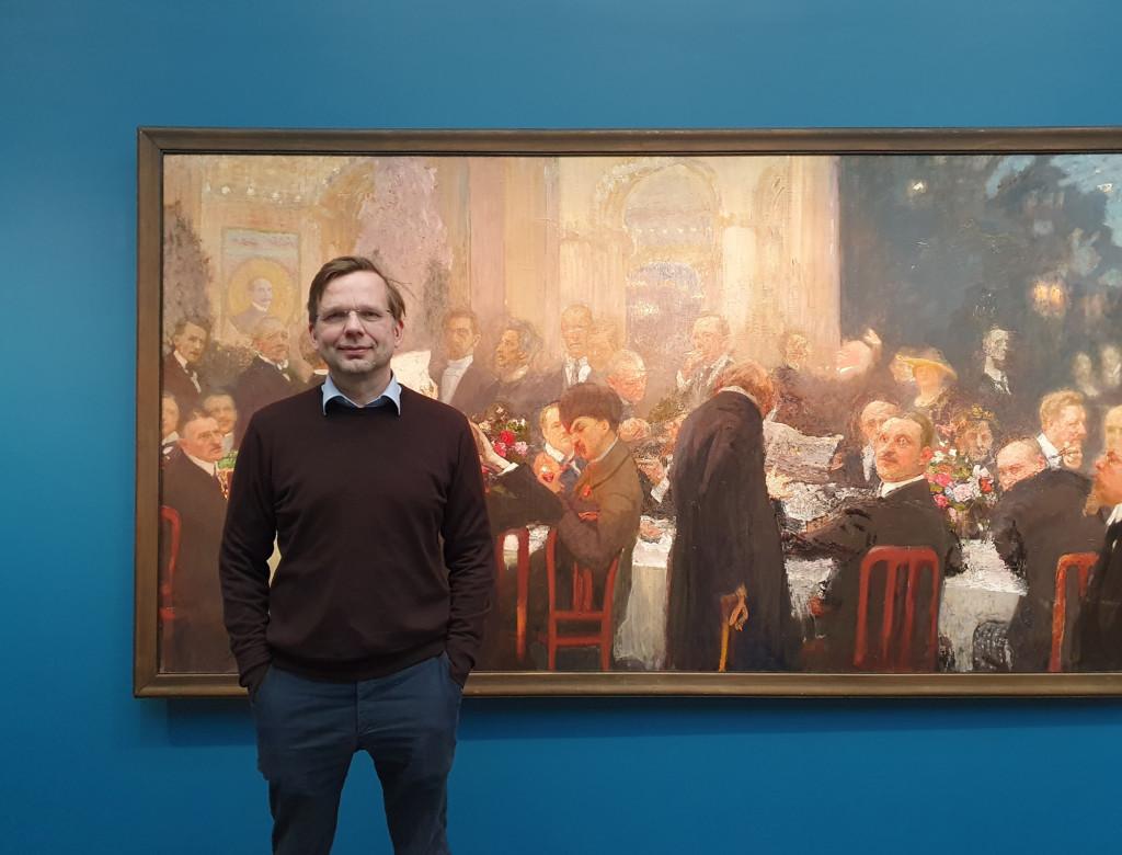 Mies seisoo Ilja Repinin Suomen suurmiehiä -taideteoksen edessä taidenäyttelyssä.