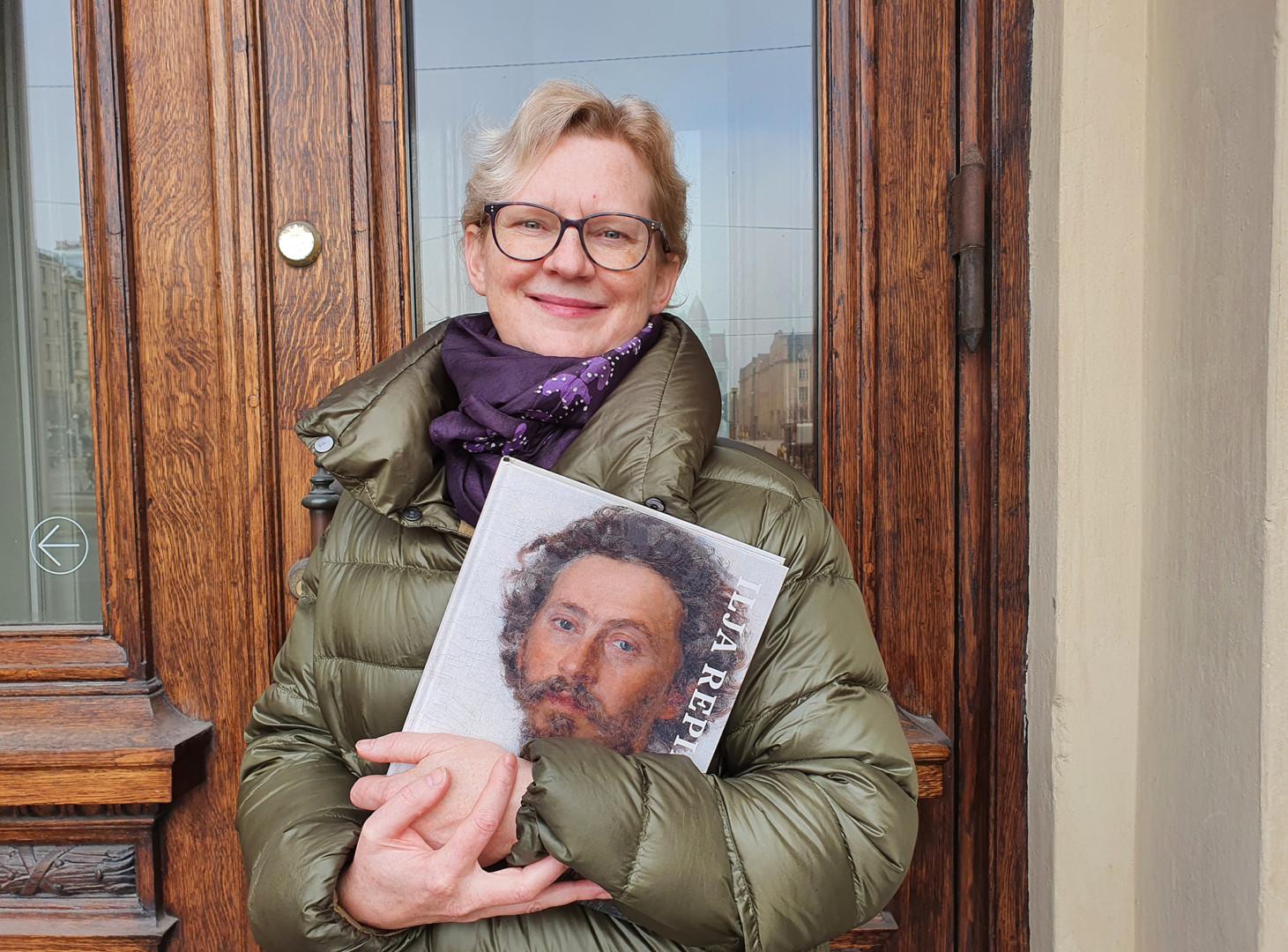 Venäjän kielen ja kulttuurin professori Sanna Turoma hymyilee Ateneumin pääovien edessä Ilja Repin -kirja kädessään.
