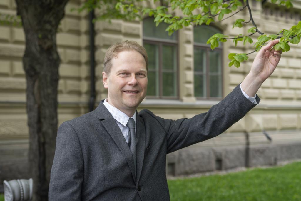 Henkilö seisoo puistossa Ateneumin ulkopuolella katsoen kameraan, harmaa puku päällä, koskettaa puun oksaa.