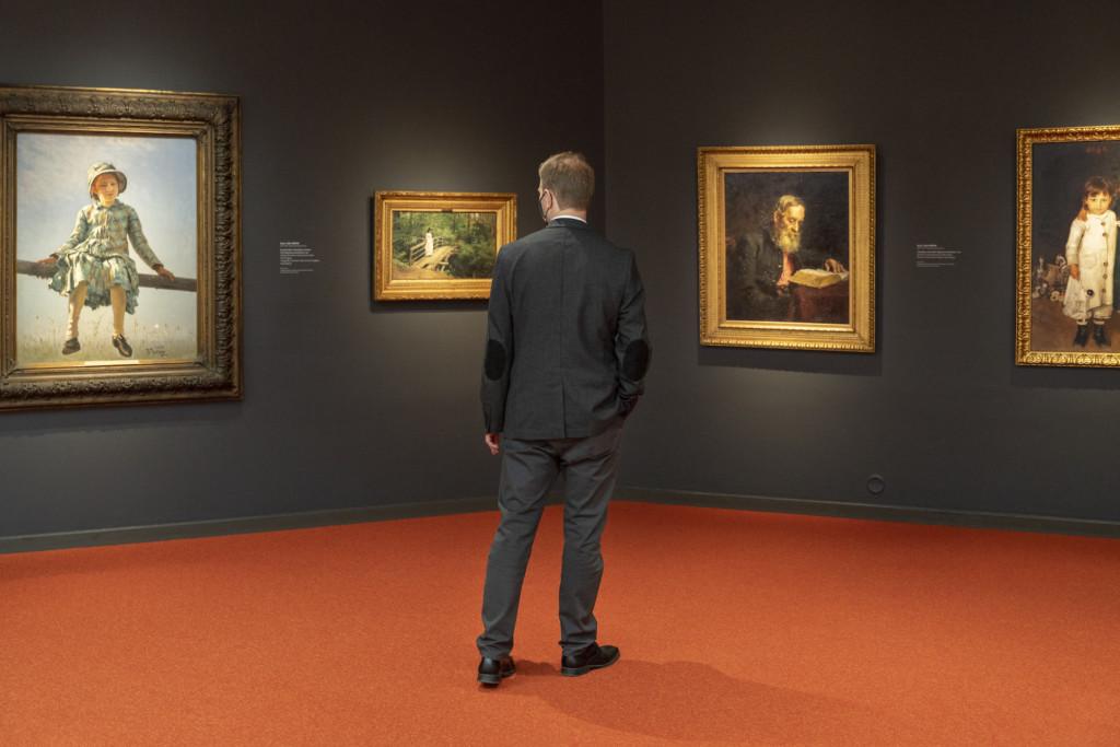 Henkilö harmaa puku päällä katsoo maalauksia taidemuseossa.