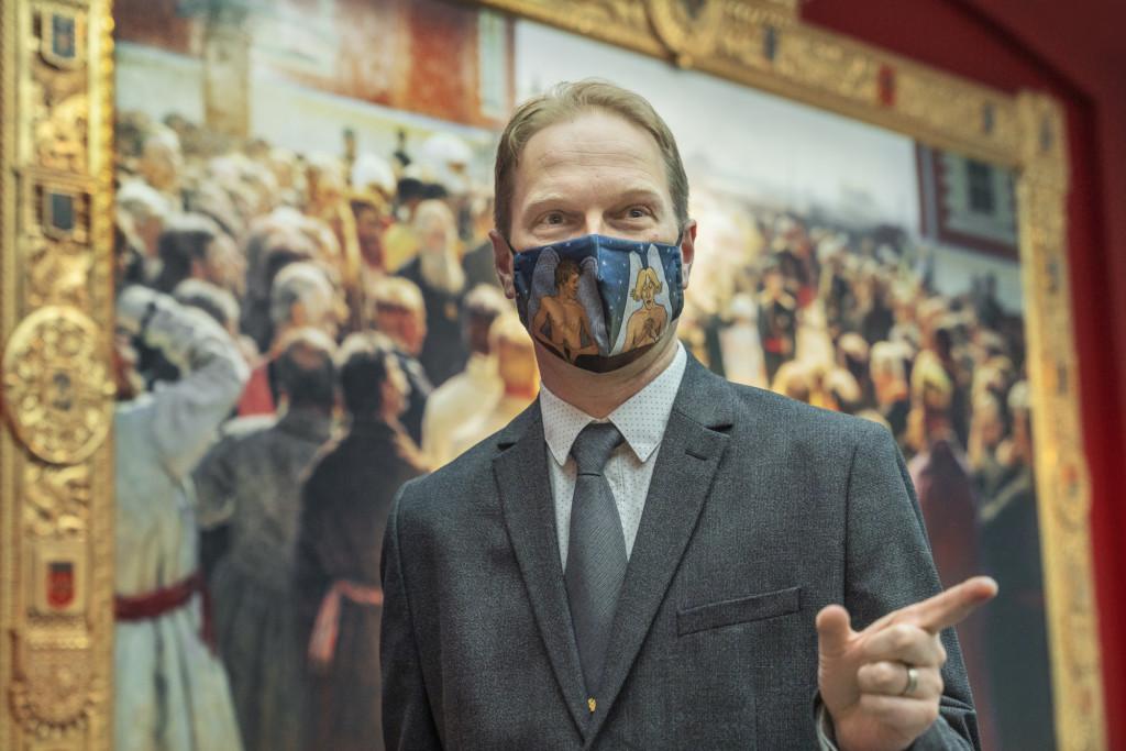 Henkilö harmaa puku päällä seisoo taidemuseossa maalauksen edessä, osoittaen sormella kuvan ulkopuolelle.