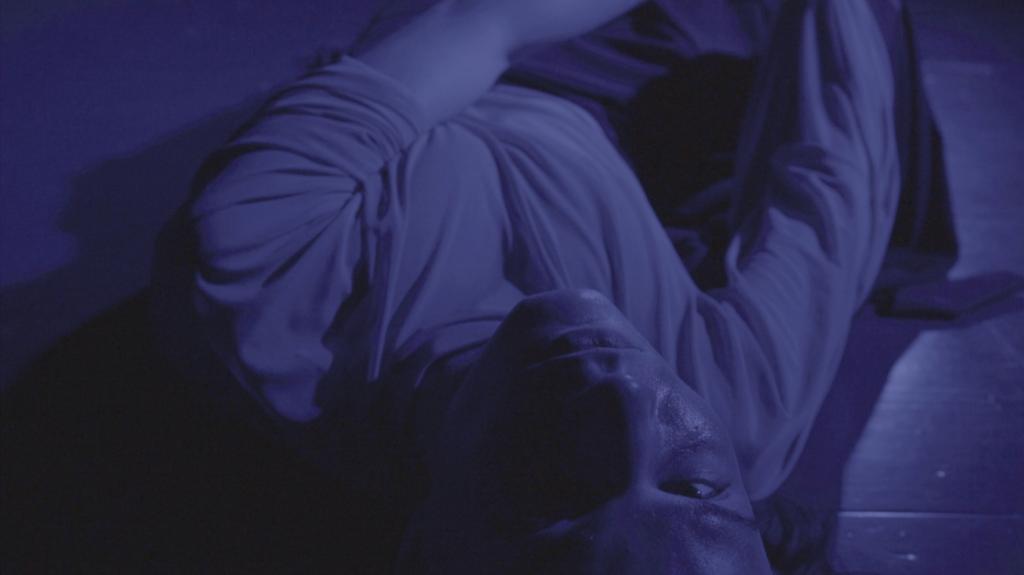 Henkilö makaa lattialla katsoen kameraan, violetiksi sävytetty kuva