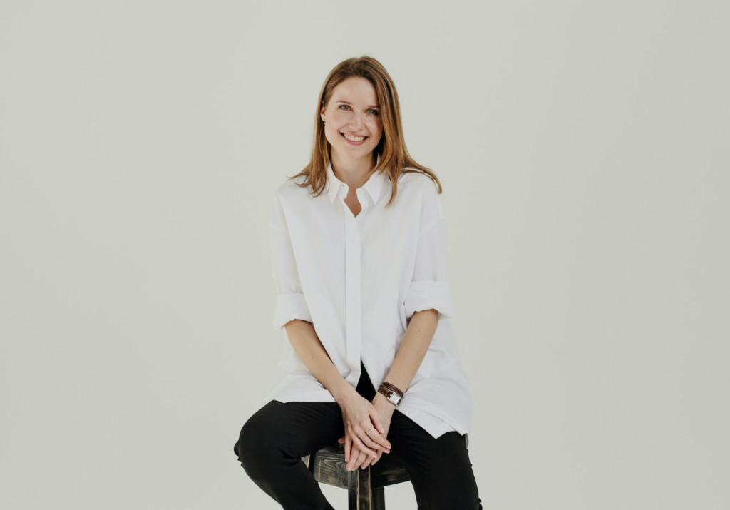 Henkilö istuu jakkaralla, hymyilee ja katsoo kameraan, yllään valkoinen kauluspaita ja mustat housut.