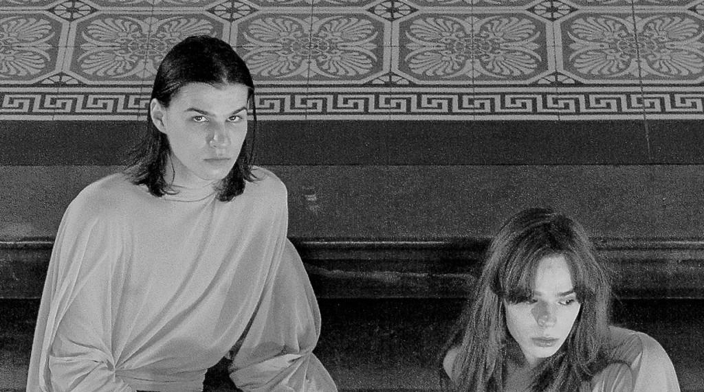 Kaksi ihmistä istuu Ateneumin pääportaikossa. Mustavalkoinen kuva.