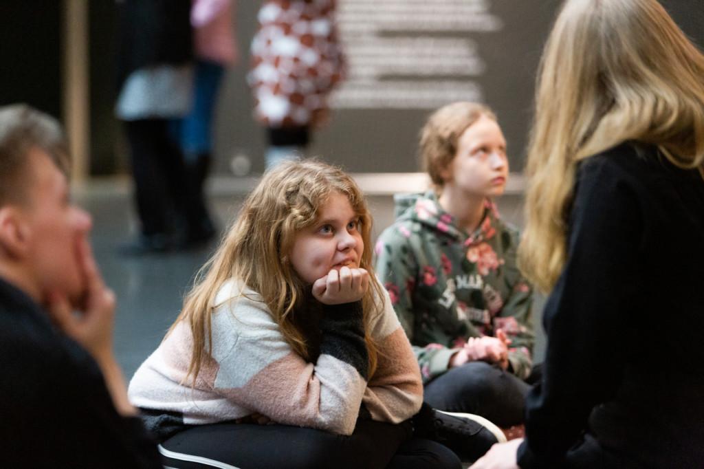 Ryhmä nuoria istuu taidenäyttelyssä lattialla. Kuvan keskellä istuva tyttö kuuntelee keskittyneesti.