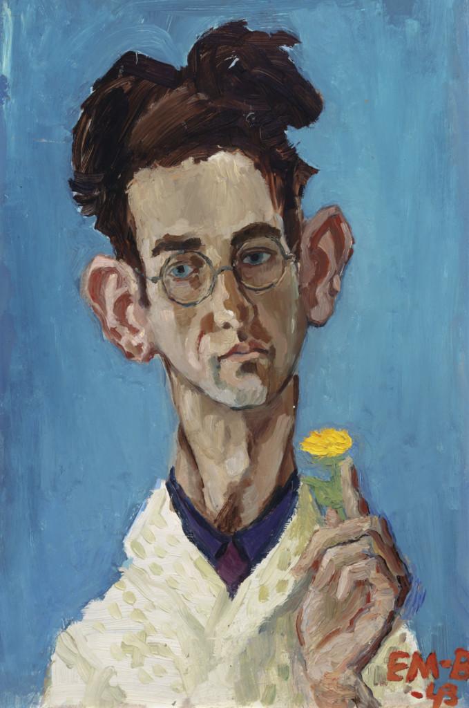 Silmälasipäinen, hörökorvainen ja tummatukkainen mies pitelee kädessään keltaista kukkaa.