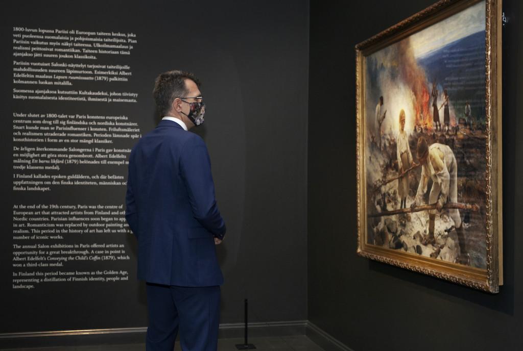 Henkilö puku päällä katsoo maalausta taidemuseossa.