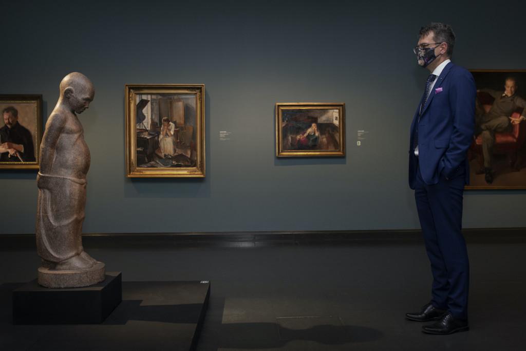 Henkilö puku päällä seisoo taidemuseossa, katsoo graniitista veistettyä taideteosta.