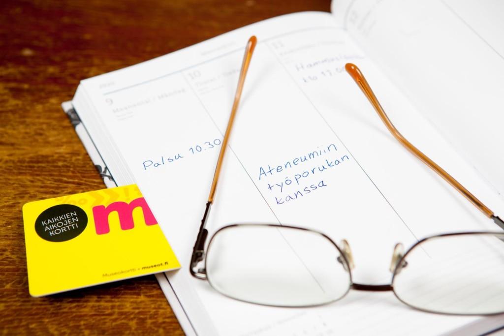 Kalenterin päällä silmälasit ja museokortti. Kalenterissa varaus porukalla Ateneumiin.