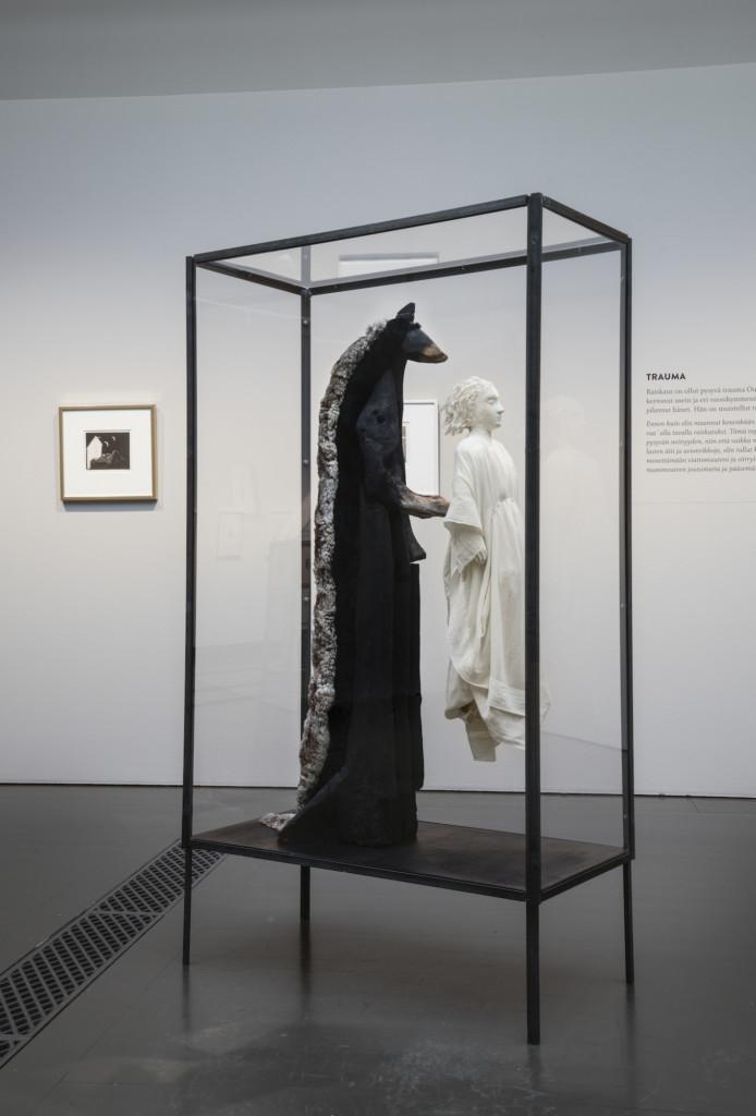Kuva veistoksesta, jossa tummasävyinen eläinhahmo pitelee vaaleansävyistä ihmishahmoa, seisten ihmishahmon takana.
