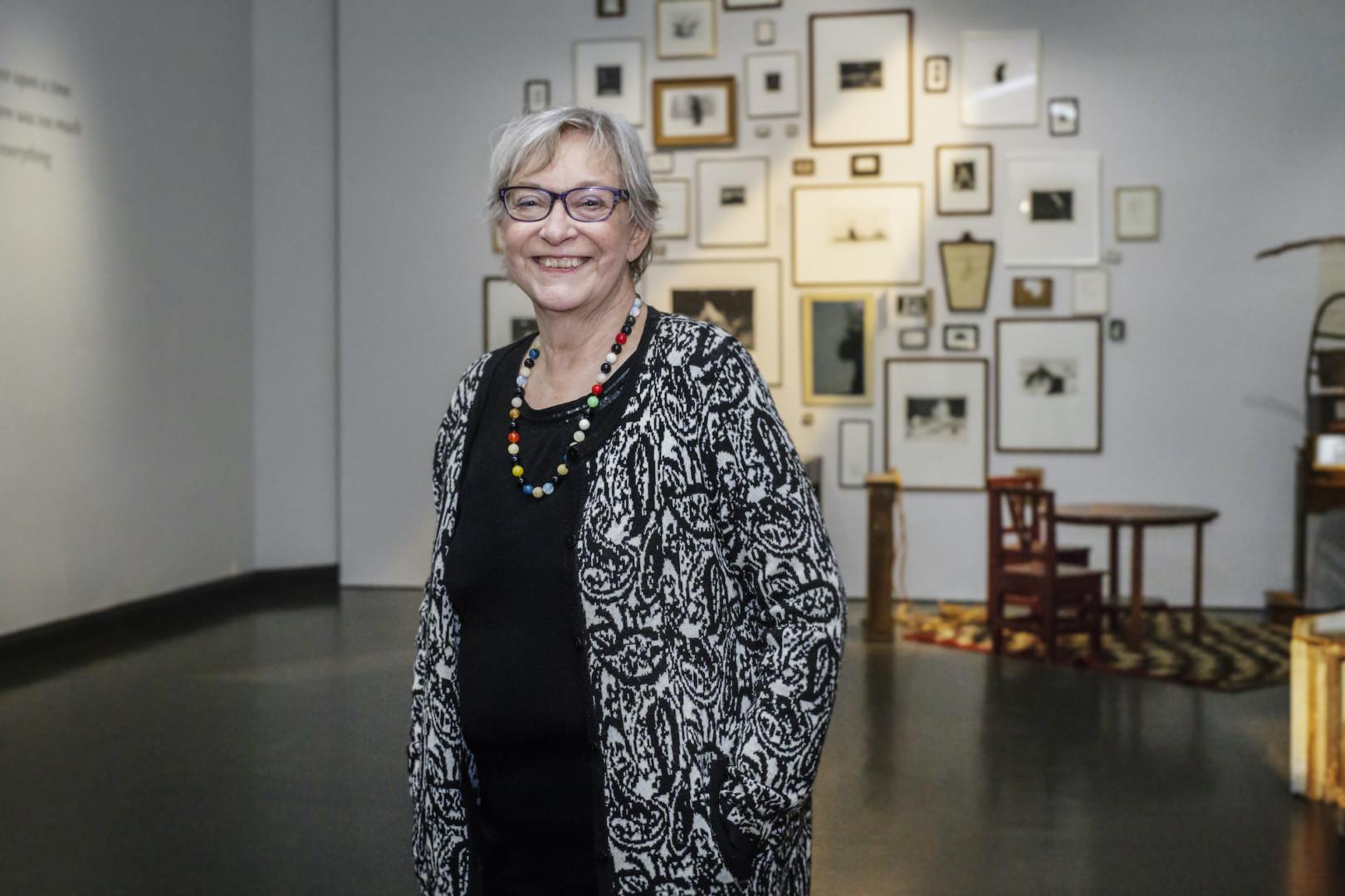 Henkilö katsoo kameraan ja hymyilee, taustalla suuri määrä grafiikan teoksia seinällä näyttelytilassa.