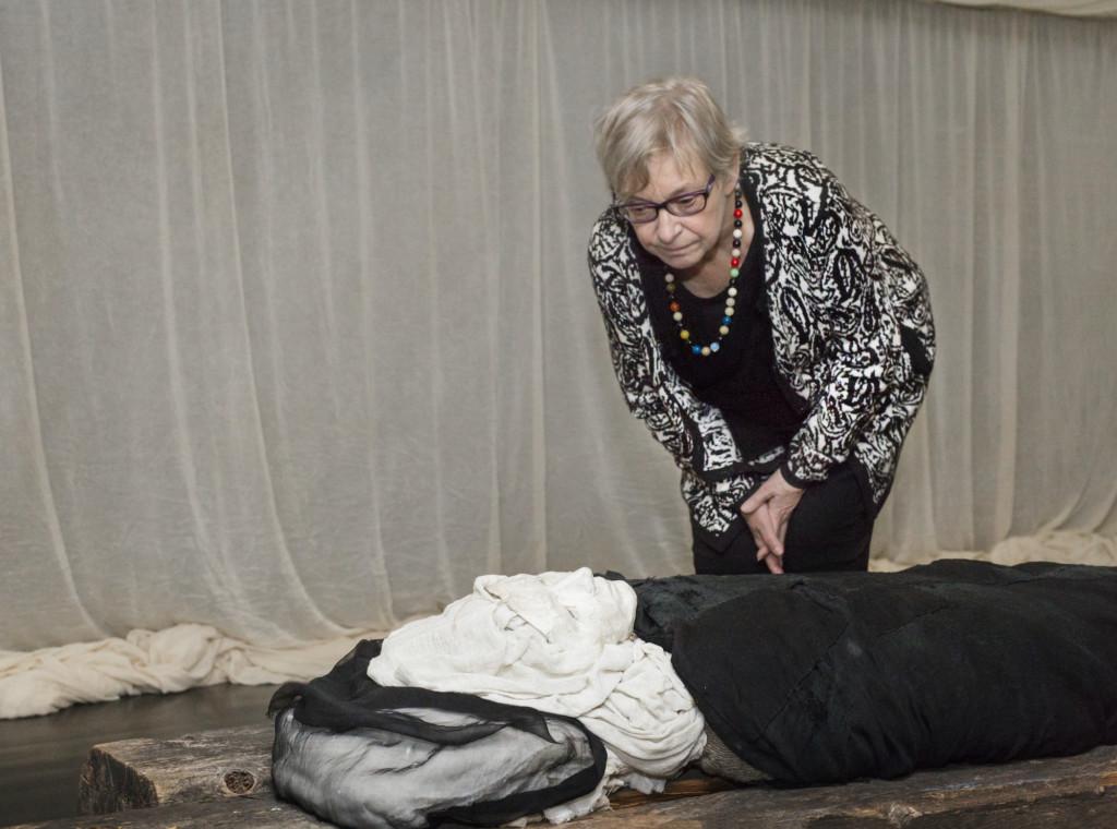 Nainen katsoo kumartuneena veistosta, joka esittää makaavaa ihmishahmoa..