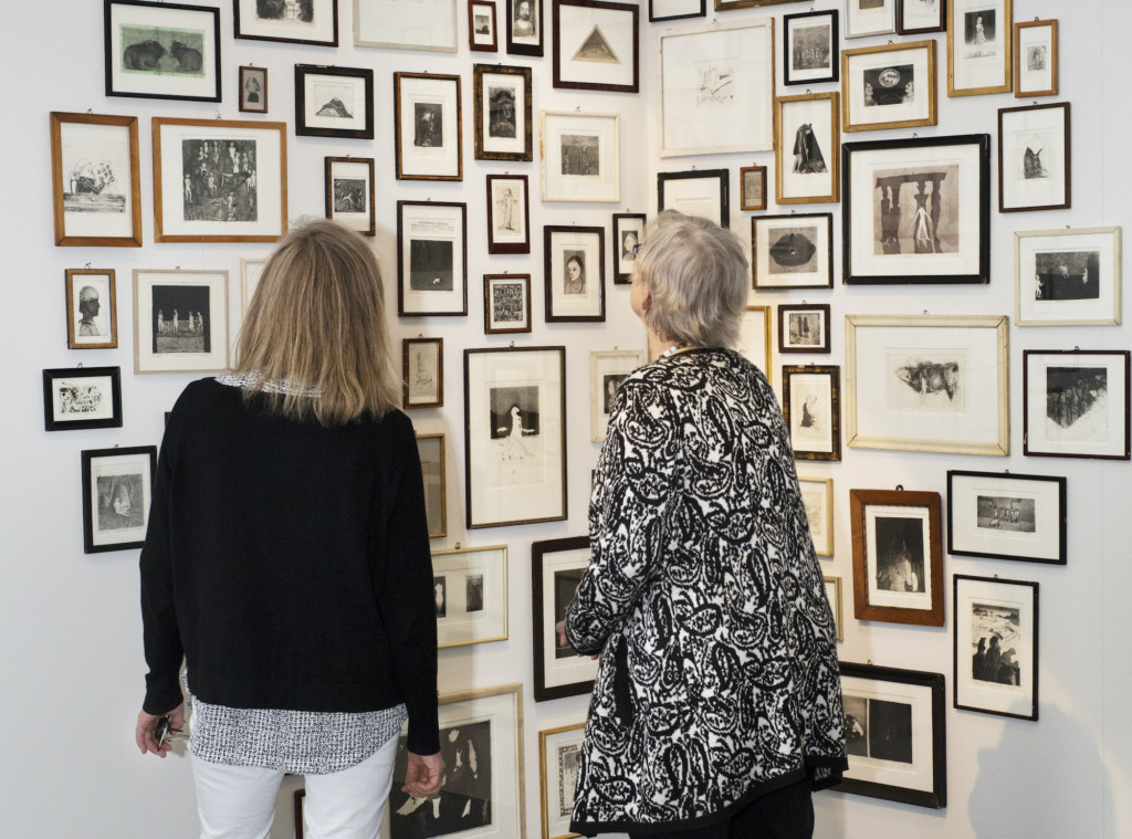 Kaksi henkilöä katsoo seinää, jossa on kymmeniä pienikokoisia grafiikan teoksia.