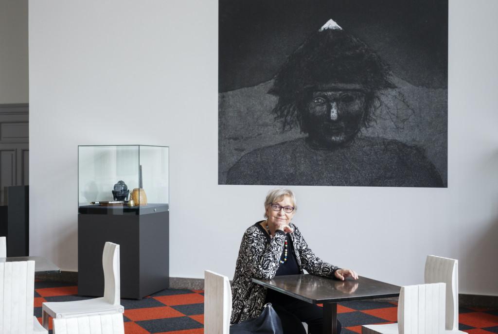 Nainen istuu pöydän äärellä, katsoo kameraan, taustalla suurikokoinen toisinto mustavalkoisesta grafiikan teoksesta.